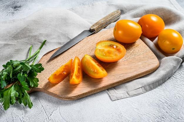 Pokrojony surowy żółty pomidor na tnącej desce. białe tło. widok z góry