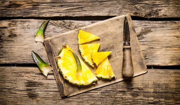 Pokrojony świeży ananas z nożem na deska do krojenia na drewnianym stole. widok z góry