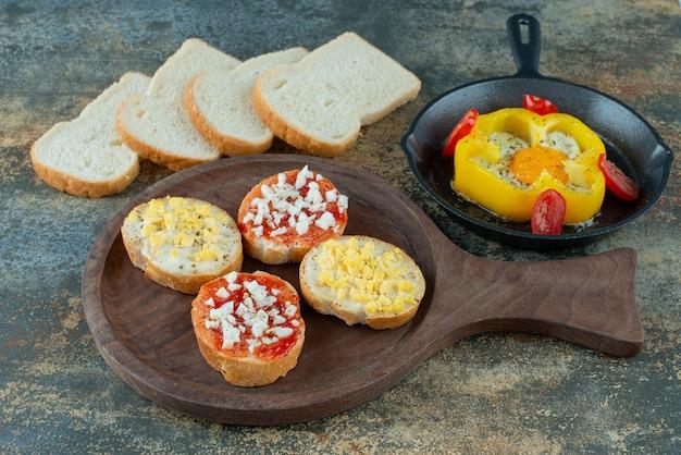 Pokrojony świeży biały chleb z jajkiem sadzonym na ciemnej patelni