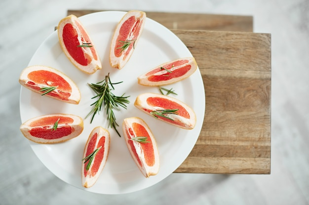 Pokrojony świeży grejpfrut i rozmaryn na białym talerzu. z góry. zdrowa dieta fitness żywności