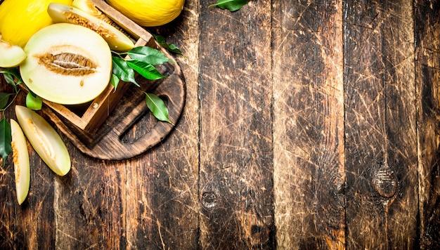 Pokrojony świeży melon w starym pudełku. na drewnianym tle.