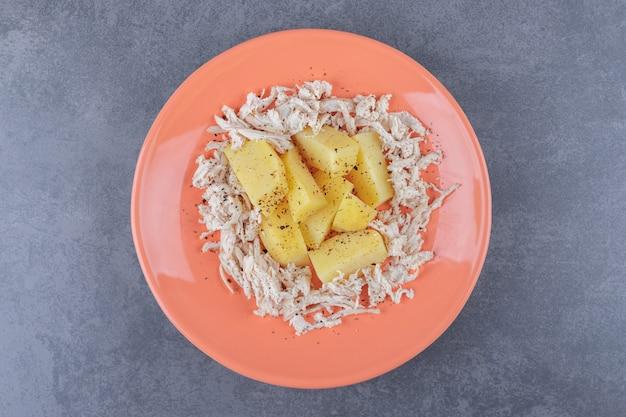 Pokrojony w kostkę kurczak z gotowanymi ziemniakami na pomarańczowym talerzu.
