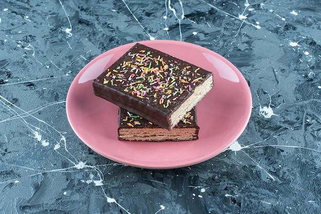 Pokrojony w plasterki wafel oblany czekoladą na talerzu, na niebieskim stole.