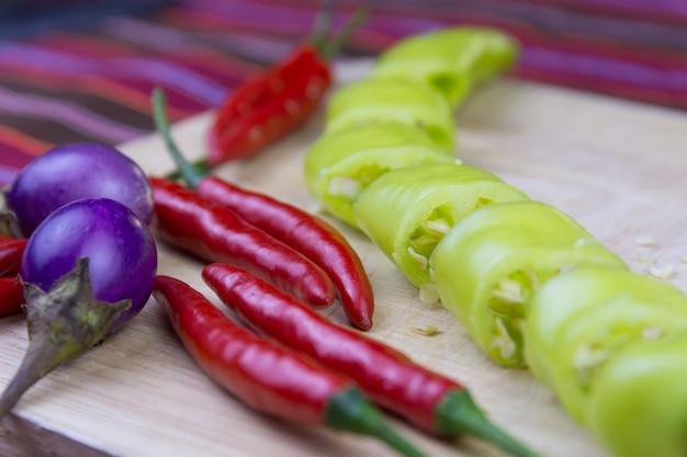 Pokrojony zielony peper, czerwony peper i oberżyna na starej drewnianej desce ,.
