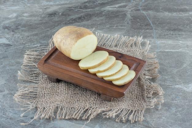 Pokrojony ziemniak na talerzu, na podstawce, na marmurowym stole.