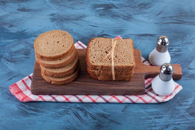 Pokrojony żytni chleb na desce na ręczniku, na niebieskiej powierzchni.