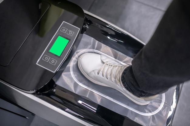Pokrowiec na buty. stopa w czystym białym tenisówce na specjalnym urządzeniu elektronicznym zakładającym ochraniacze na buty
