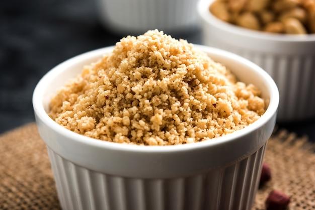 Pokruszone orzeszki ziemne lub proszek mungfali z całymi prażonymi orzeszkami ziemnymi. podawane w misce na nastrojowym tle. selektywne skupienie
