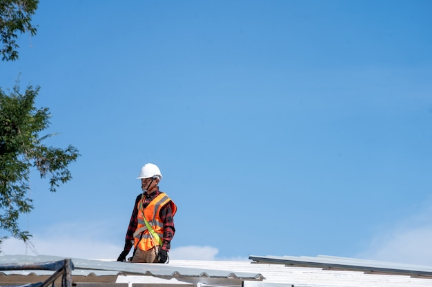 Pokrycia dachowe, robotnicy budowlani noszący sprawdzanie uprzęży bezpieczeństwa i montaż instalacji nowego dachu, narzędzia dekarskie.