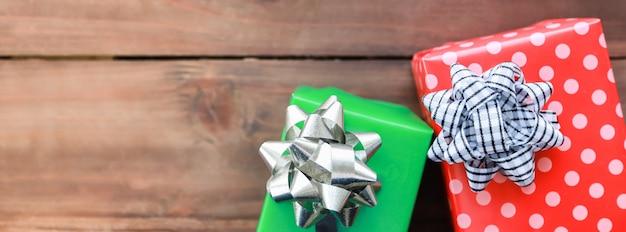 Pokrycie koncepcji nowego sezonu świątecznego i świątecznego. zamyka up kolorowy dwa prezenta pudełko z pięknym faborkiem na drewnianej desce z kopii przestrzenią.