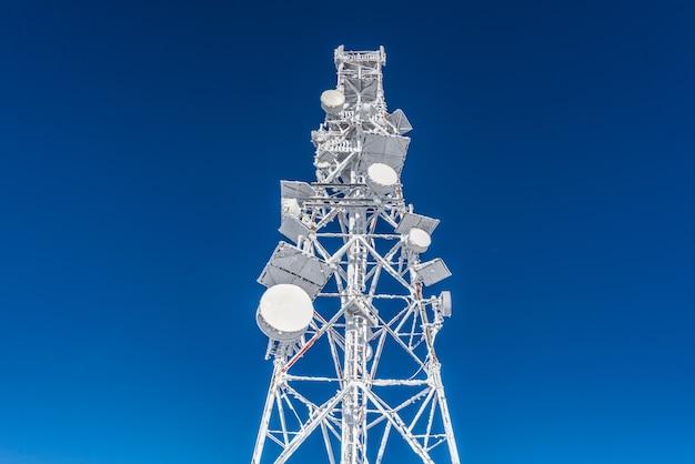 Pokryta lodem wieża komórkowa na dachu stacji bazowej znajdującej się na wyżynach. stacja telefonii komórkowej.