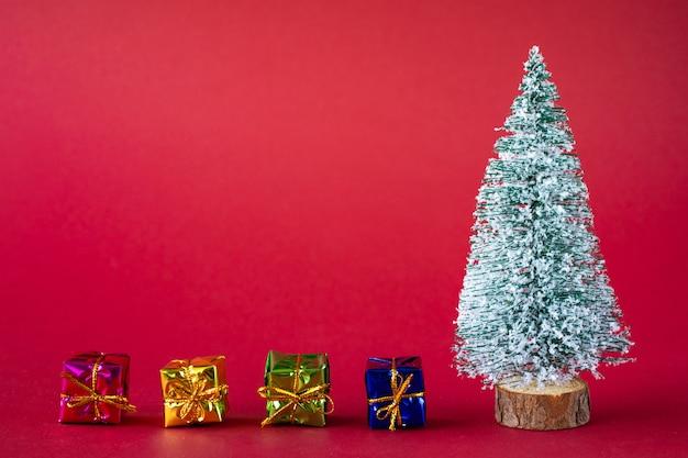 Pokryta śniegiem choinka i jasne, wielokolorowe pudełka z prezentami