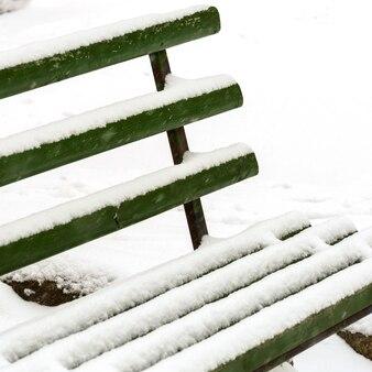 Pokryta śniegiem ławka w parku