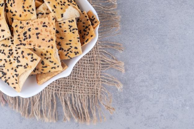 Pokryte sezamem kromki chleba na talerzu na kawałku materiału na marmurowym stole.