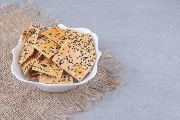 Pokryte sezamem kromki chleba w misce na kawałku materiału na marmurowym stole.
