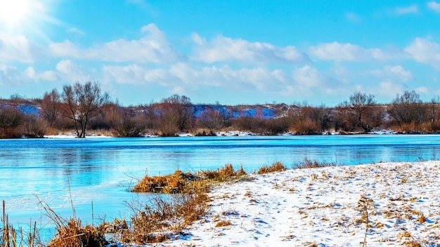 Pokryte śniegiem brzeg rzeki i rzeka z błękitną wodą w słoneczną pogodę