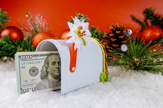 Pokryte śniegiem dekoracje świąteczne z gałęzi sosny szyszki na skrzynce pocztowej na prezent dolary amerykańskie
