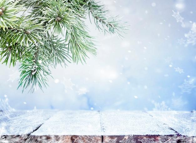 Pokryte śniegiem deski drewniane i gałąź sosny na zewnątrz w śniegu