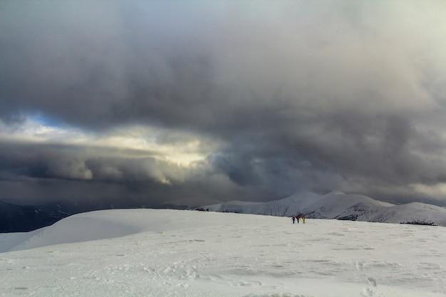 Pokryte śniegiem górskie wzgórza karpackie z turystami daleko turystów w zimie