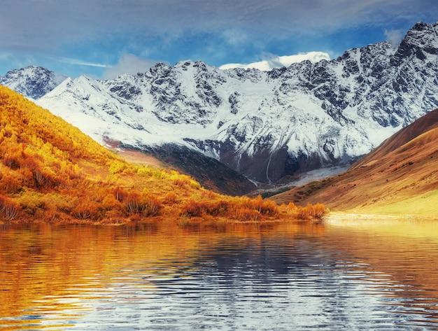 Pokryte śniegiem góry we mgle. jesień nad jeziorem koruldi