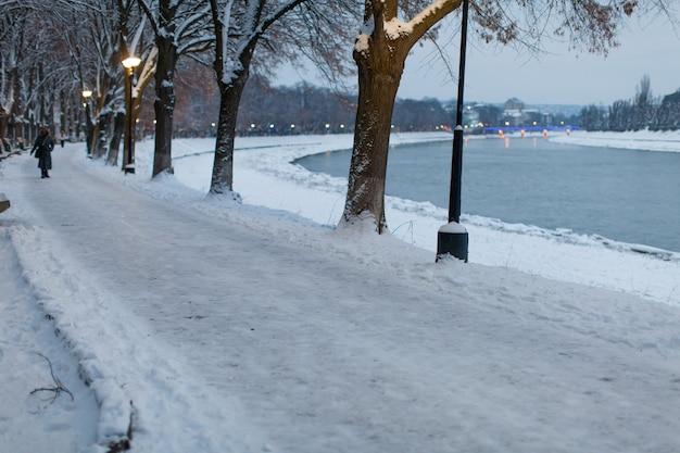 Pokryte śniegiem nasyp w mieście wieczorem. piękny zimowy krajobraz