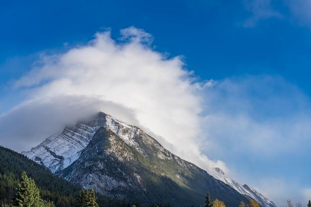 Pokryte śniegiem pasmo górskie mount rundle z zaśnieżonym lasem nad błękitnym niebem i białymi chmurami w zimie