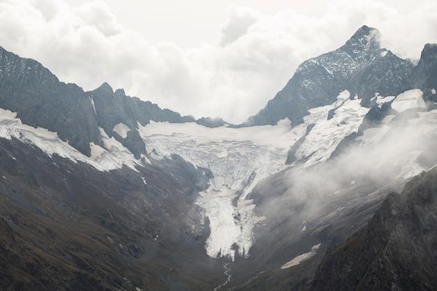 Pokryte śniegiem pasmo górskie w chmurach. dolina z górskim potokiem. kaukaz, rosja