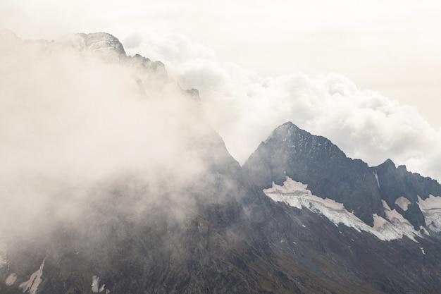 Pokryte śniegiem pasmo górskie w chmurach. kaukaz, rosja.