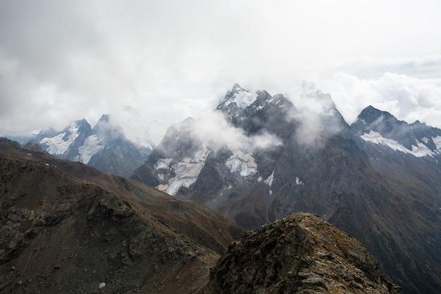 Pokryte śniegiem pasmo górskie w chmurach. kaukaz, rosja