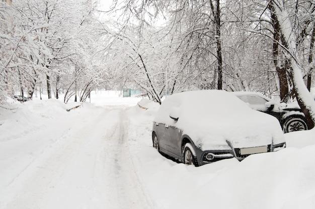 Pokryte śniegiem samochody na tle opuszczania stoczni.