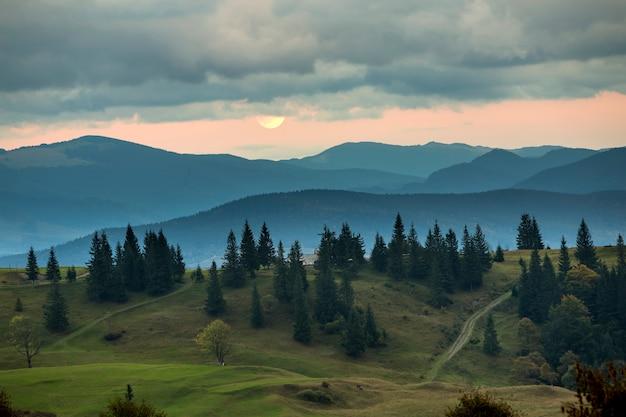 Pokryty górami mgły przy wschodzie księżyca, duży księżyc na jasnym pomarańczowym niebie nad wysokimi jodłami.