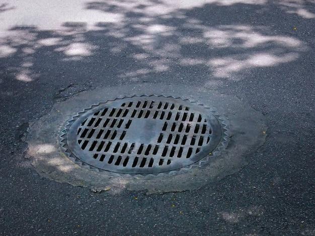 Pokrywa okrągłego włazu z metalową kratą do odprowadzania wody deszczowej