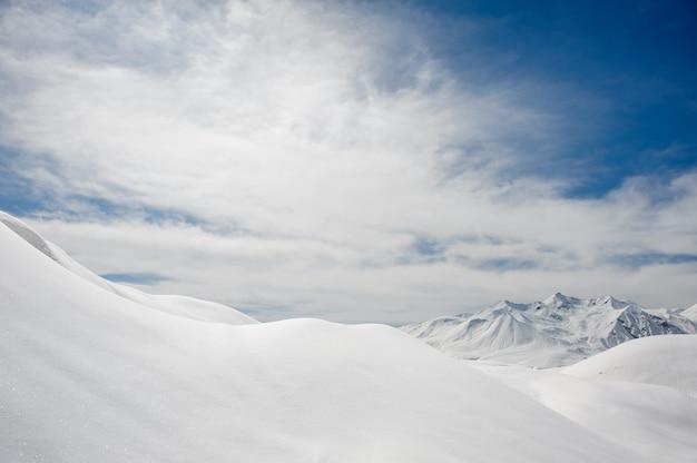 Pokrywa śnieżna i ośnieżone szczyty górskie na tle błękitnego nieba