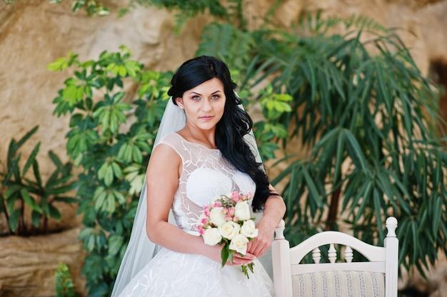 Pokusa model brunetki panny młodej w ekscytującej sukni ślubnej z bukietem pod ręką w pobliżu białego krzesła