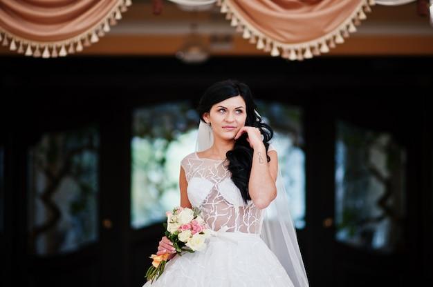 Pokusa model brunetki panny młodej w ekscytującej sukni ślubnej z bukietem pod ręką z tatuażem nieskończoności w hali