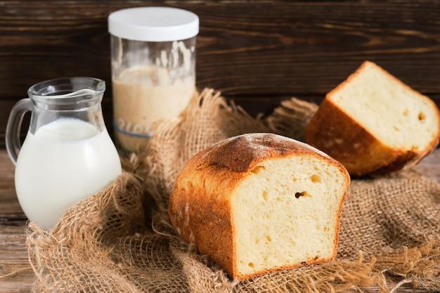 Pół bochenka domowego chleba na zakwasie, selektywna ostrość. na stole zakwas i karafka mleka. close-up, z miejsca na kopię. wypiekaj chleb na wyściółce z tkaniny, na drewnianej ścianie