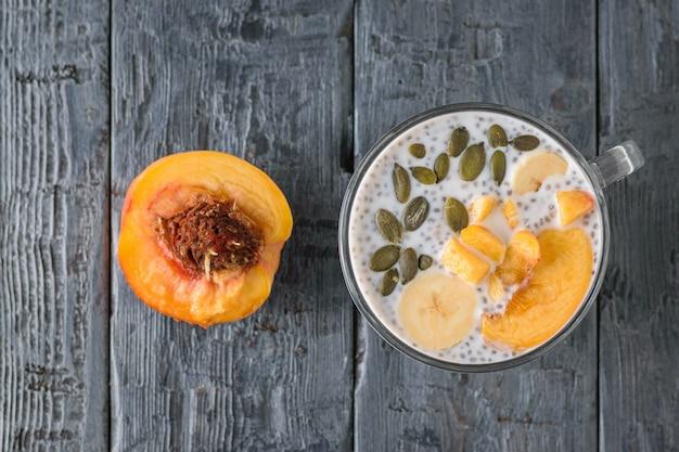 Pół brzoskwini i budyń z czarnymi nasionami chia na wiejskim stole. widok z góry. leżał płasko.