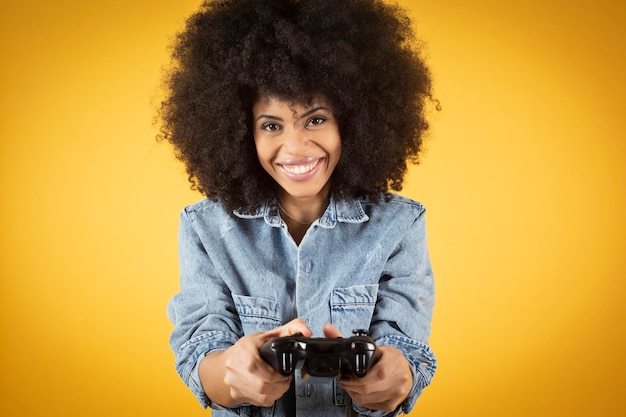 Pół ciała obraz młodej szalonej podekscytowanej szczęśliwej afrykańskiej kobiety, grającej w gry wideo, siedzącej na fotelu na białym tle