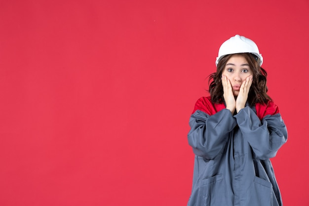 Pół ciała strzał niepewnej emocjonalnej kobiety budowniczego w mundurze z twardym kapeluszem na na białym tle czerwonym tle