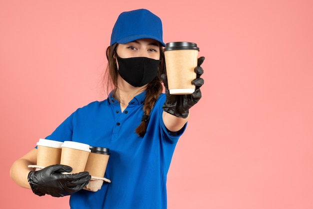 Pół ciała strzał pewnie kurier dziewczyna nosi czarne rękawiczki medyczne maski trzymając kawę na pastelowym tle brzoskwini