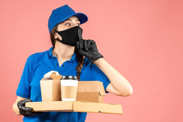 Pół ciała strzał zdezorientowanej kurierskiej dziewczyny w masce medycznej i rękawiczkach trzymających zamówienia na pastelowym tle brzoskwiniowym