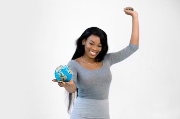 Pół długości portret podekscytowanej afrykańskiej dziewczyny w szarej sukience trzymającej rękę do góry, trzymającej kulę ziemską