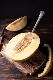 Pół dojrzały melon z nasionami i łyżką na deskę do krojenia na ciemnym tle drewnianych.