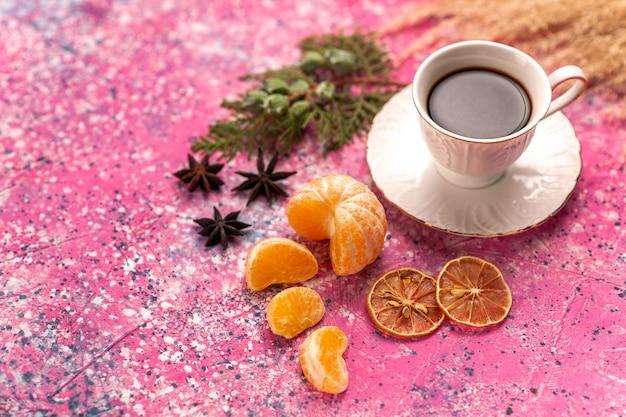 Pół-góra bliska filiżanka herbaty z mandarynkami na jasnoróżowym biurku.
