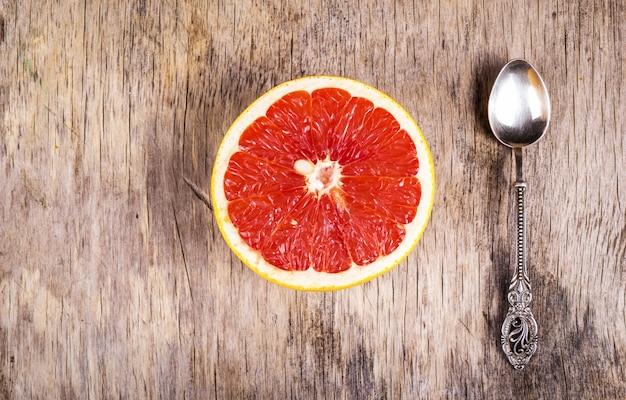 Pół grejpfruta i srebrną łyżeczkę na starym drewnianym tle. zdrowe śniadanie. utrata tłuszczu i detoksykacja. skopiuj miejsce