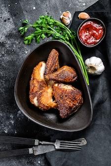 Pół kurczaka z grilla na talerzu. czarne tło. widok z góry