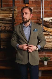 Pół obrotu poważny pewny siebie zarost w nowoczesnej kurtce stojący przy ścianie z cegły w aparacie na poddaszu