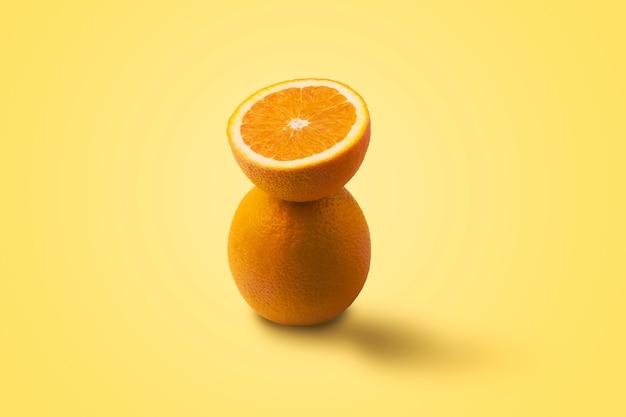 Pół plasterki pomarańczy balansują na jednej całej pomarańczy na żółtym tle