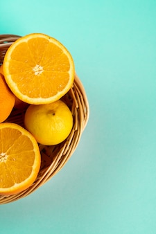 Pół pomarańczy i cytryny w wiklinowym koszu na stole