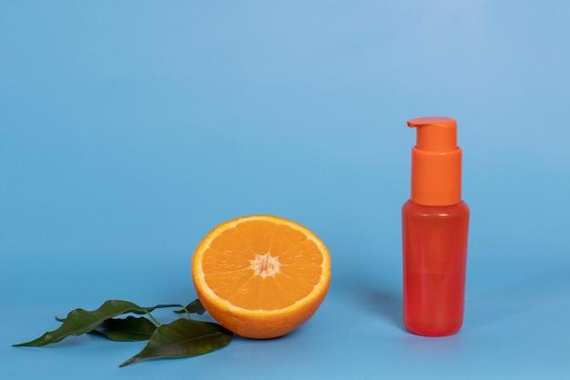 Pół pomarańczy z ulotkami i butelką kosmetyczną z balsamem, kremem, lakierem do ciała i włosów. koncepcja naturalnej higieny owoców cytrusowych.